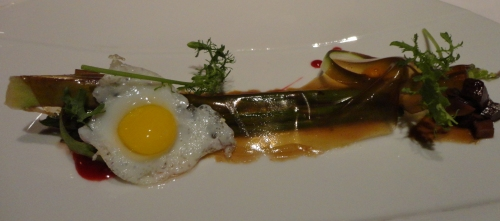 Asparagus served with  porcini mushrooms and a quail egg, topped with a hollandaise sauce, and a Balsamic reduction sheet.