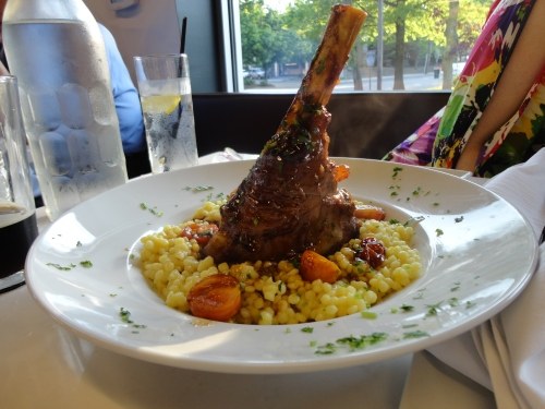 Lamb Shank cradled by pearled cous cous, topped with a sherry wine reduction sauce